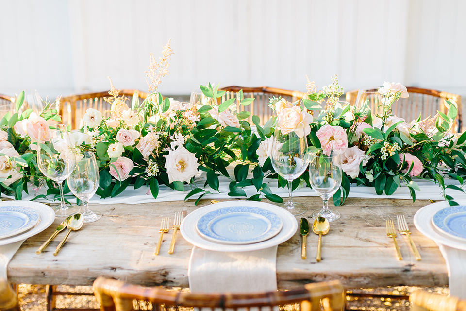 wooden farm table with blue plates and floral centerpieces