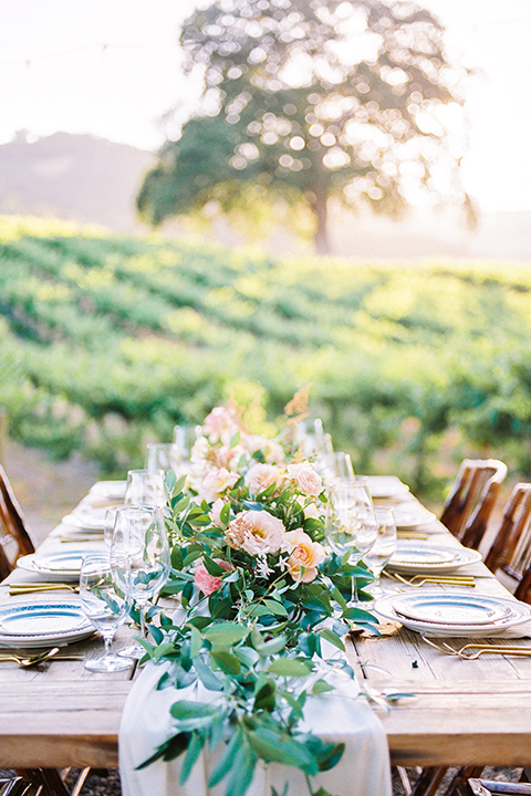 farm table with white table runner and garden florals as a center piece