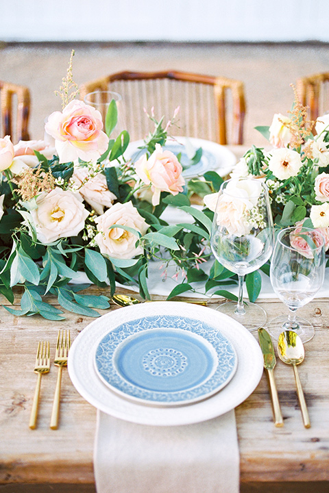 white charger plates with blue plates and gold flatware