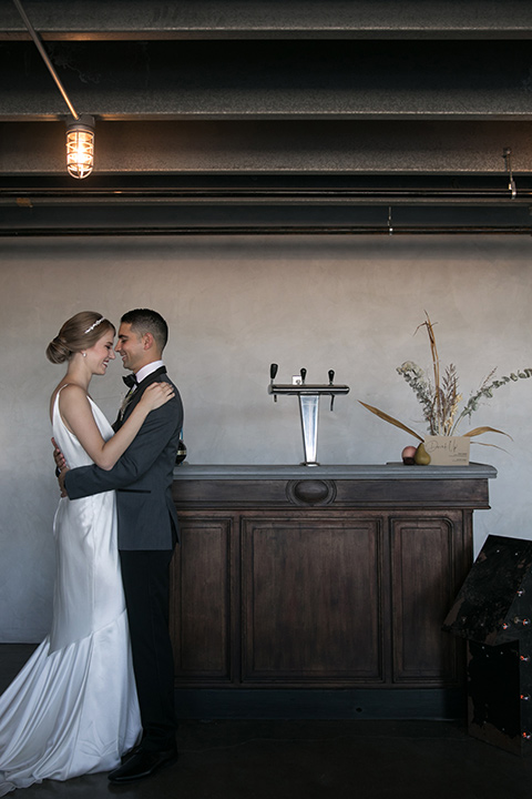 the bride in a satin form fitting gown with straps and a plunging neckline and the groom in a grey tuxedo with a black shawl lapel and black bow tie by bar
