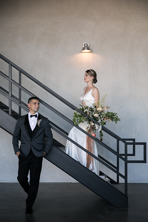 the bride in a satin form fitting gown with straps and a plunging neckline and the groom in a grey tuxedo with a black shawl lapel and black bow tie by stairs