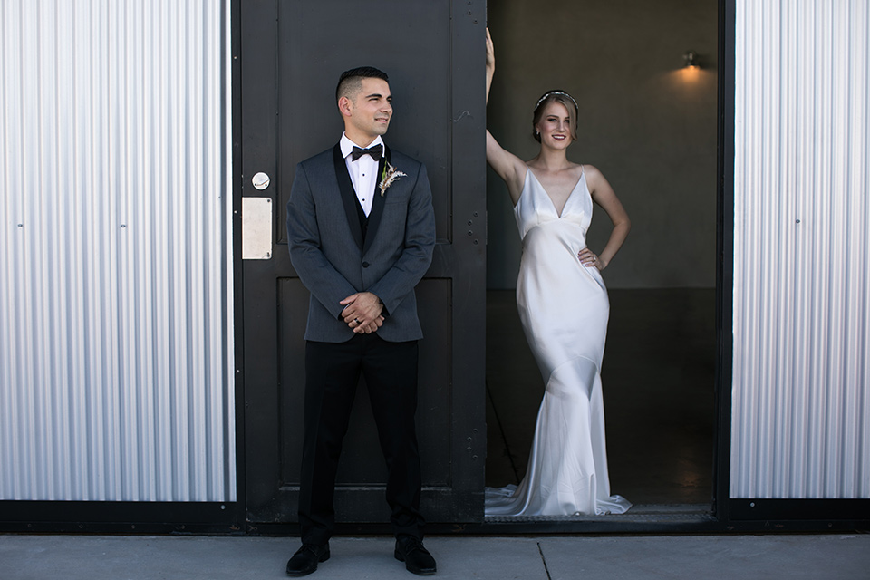 the bride in a satin form fitting gown with straps and a plunging neckline and the groom in a grey tuxedo with a black shawl lapel and black bow tie outside venue