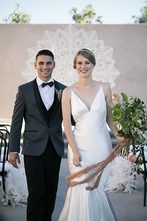 the bride in a satin form fitting gown with straps and a plunging neckline and the groom in a grey tuxedo with a black shawl lapel and black bow tie at ceremony walking down the aisle