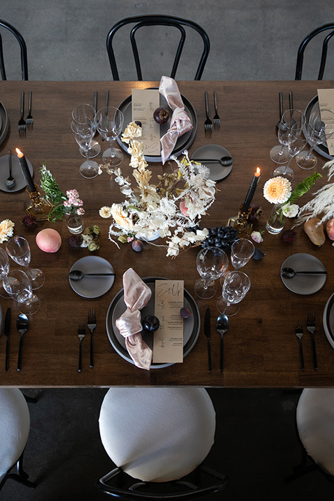 dark wooden chairs and table and feather and gold accessories