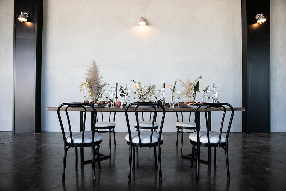 dark wooden table with feather centerpieces and chairs