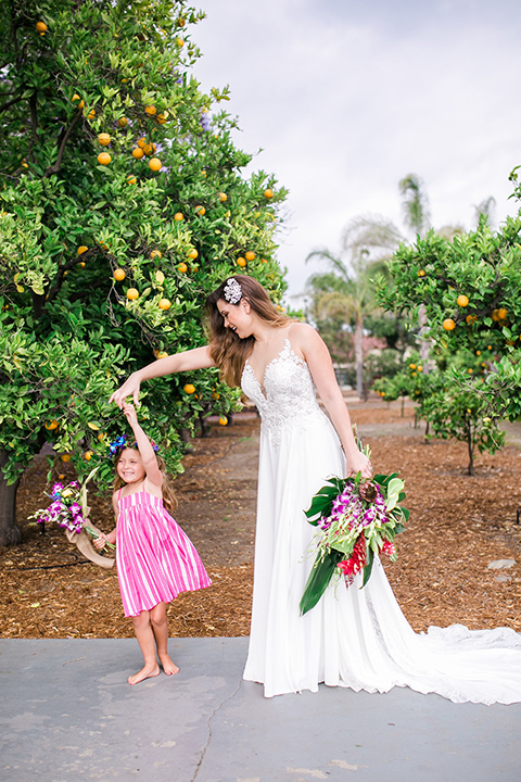 bride holding a tropical floral bouquet in her boho gown and floral headband with flower girl in a pink dress and matching headband