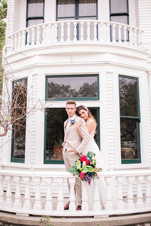 bride in a boho style gown with a bright colored floral crown and the groom in a tan suit with a tan long tie by a white building