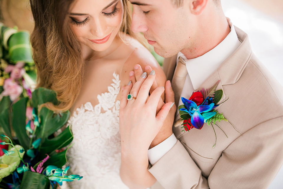 bride in a boho style gown with a bright colored floral crown and the groom in a tan suit with a tan long tie close up