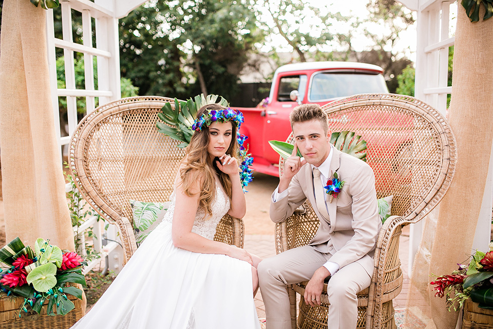 bride in a boho style gown with a bright colored floral crown and the groom in a tan suit with a tan long tie sitting in big chairs