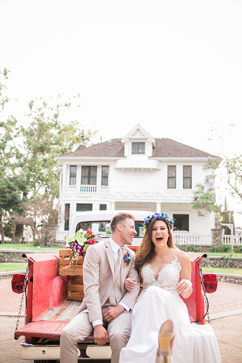 bride in a boho style gown with a bright colored floral crown and the groom in a tan suit with a tan long tie in the bed of a truck