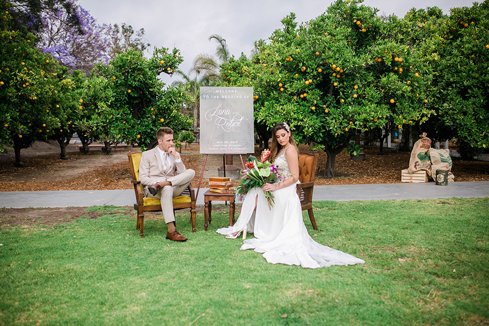 bride in a boho style gown with a bright colored floral crown and the groom in a tan suit with a tan long tie sitting in chairs outside on the grass