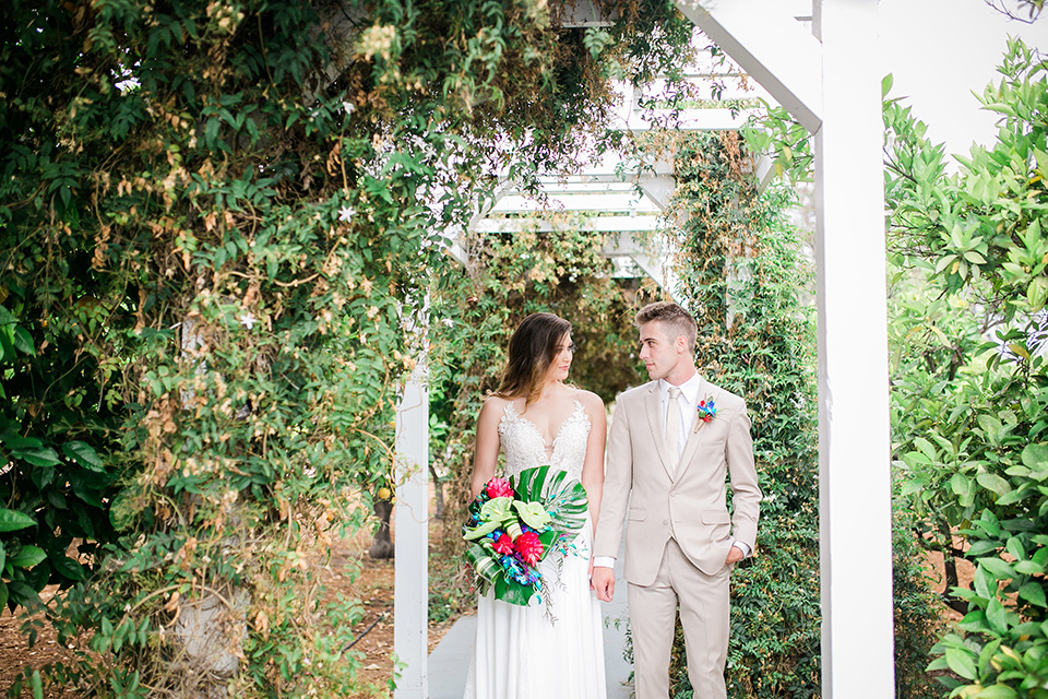 bride in a boho style gown with a bright colored floral crown and the groom in a tan suit with a tan long tie walking outside