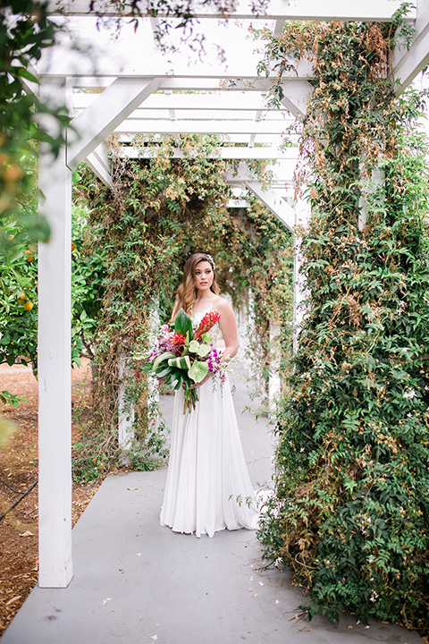 the bride in a boho style gown with straps and a bright colored floral headband