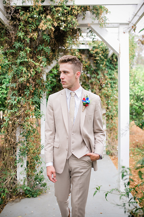the groom in a tan suit with a tan long tie walking outside