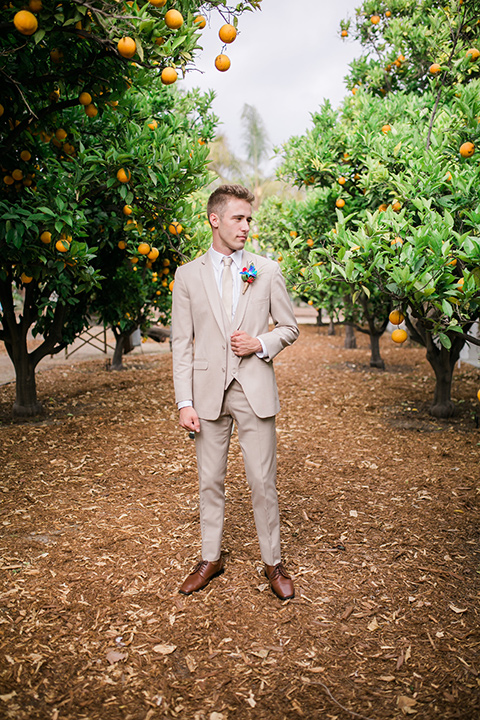 the groom in a tan suit with a tan long tie