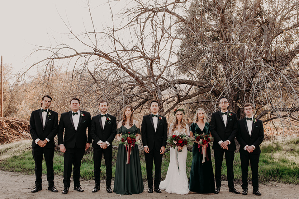 Highway-West-Vacations-bridal-party-all-lined-up-bridesmaids-in-dark-green-dresses-groomsmen-in-black-tuxedos-with-green-velvet-bow-ties-bride-in-a-lace-bohemian-dress-with-sleeves-and-floral-crown-groom-in-a-black-tuxedo