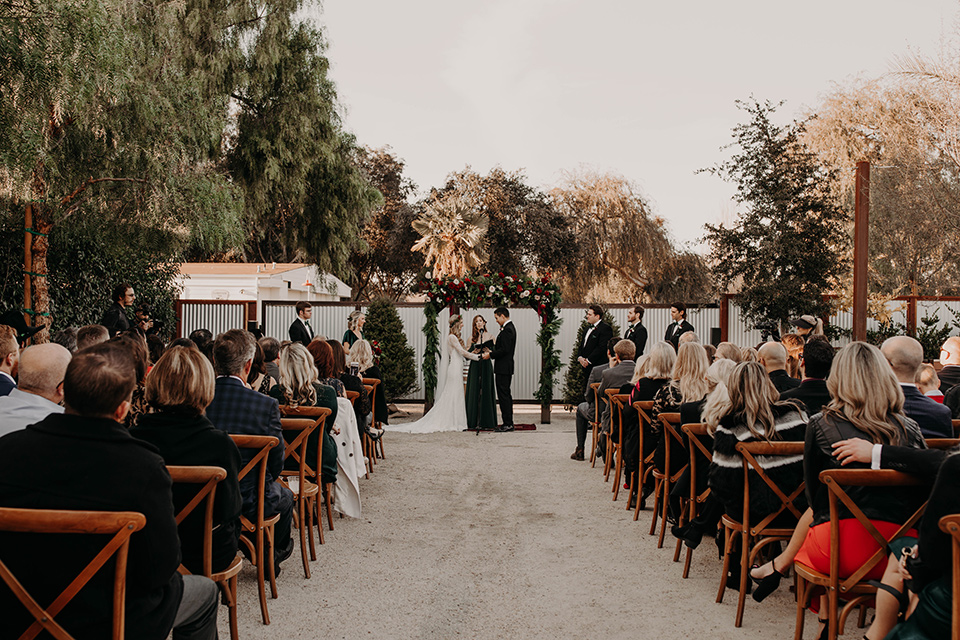 Highway-West-Vacations-bride-and-groom-ceremony-bridesmaids-in-dark-green-dresses-groomsmen-in-black-tuxedos-with-green-velvet-bow-ties-bride-in-a-lace-bohemian-dress-with-sleeves-and-floral-crown-groom-in-a-black-tuxedo