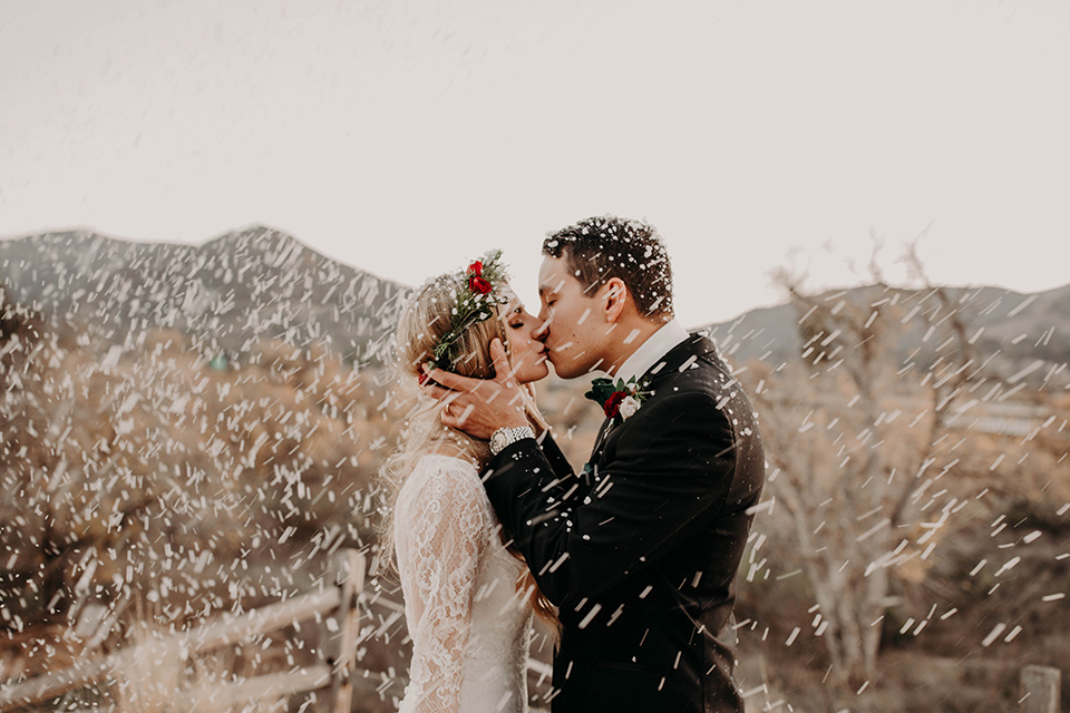 Highway-West-Vacations-bride-and-groom-kissing-in-the-snow-kissing-bride-in-a-lace-bohemian-dress-with-sleeves-and-floral-crown-groom-in-a-black-tuxedo