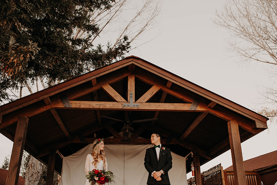 Highway-West-Vacations-bride-and-groom-under-gazebo-bride-in-a-lace-bohemian-dress-with-sleeves-and-floral-crown-groom-in-a-black-tuxedo