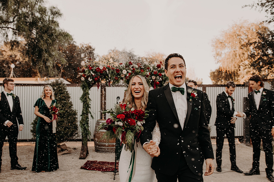 Highway-West-Vacations-bride-and-groom-with-snow-bride-in-a-lace-bohemian-dress-with-sleeves-and-floral-crown-groom-in-a-black-tuxedo