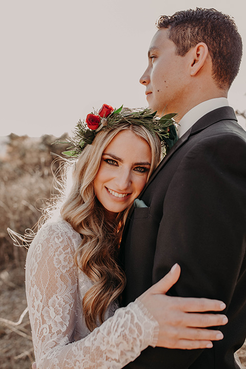 Highway-West-Vacations-bride-on-grooms-chest-bride-alone-in-a-lace-gown-with-sleeves-and-a-floral-crown-groom-in-a-black-tuxedo-with-a-velvet-bow-tie