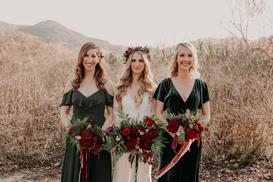 Highway-West-Vacations-bridesmaids-in-deep-green-dresses-bride-in-a-long-sleeved-lace-gown-with-a-floral-crown