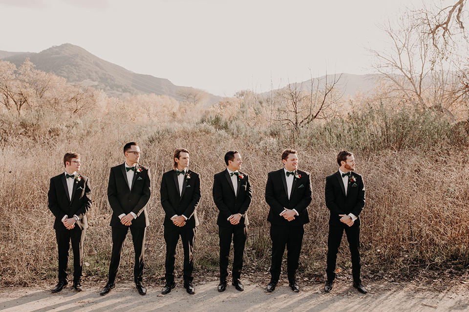 Highway-West-Vacations-groomsmen-in-black-tuxedos-with-velvet-bow-ties