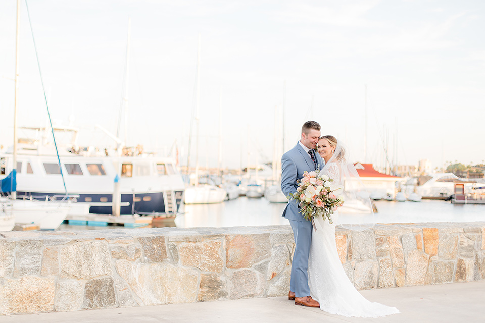 Bride and groom pose in front of the Coronado Harbor