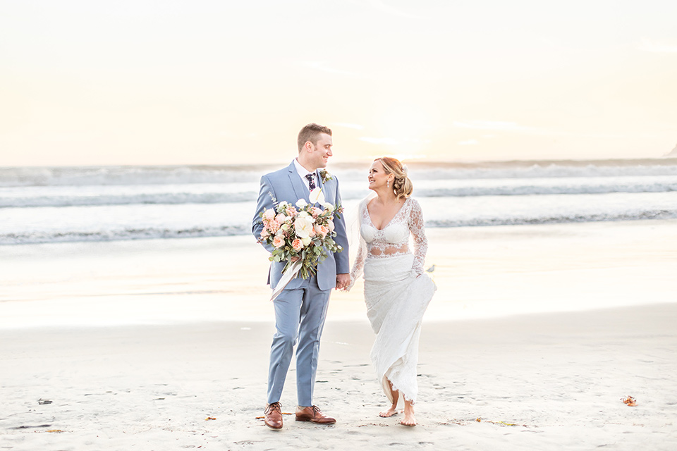 Bride and groom look each other in the eyes as they walk down the beach