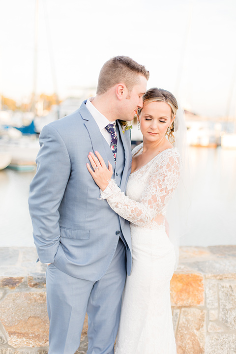 Bride and groom embrace each other in front of harbor