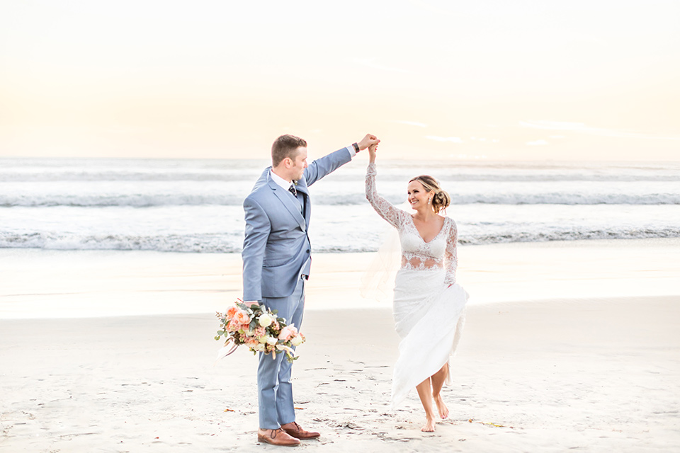 Bride and groom dance on the beach in their outfits