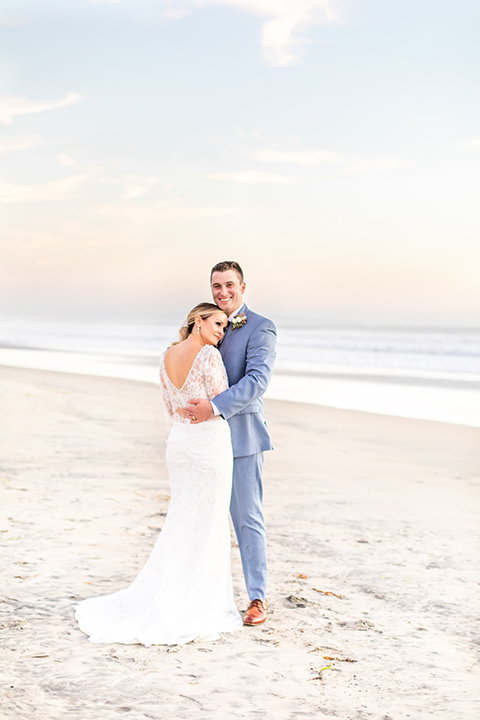 Bride and groom pose for a sunset beach wedding photo