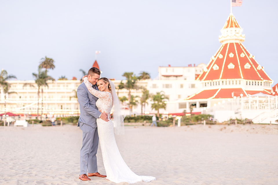 Bride and groom pose for a wedding photo in front of the Hotel Del Coronado