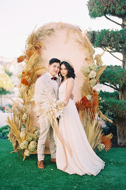 bride in a cream colored bohemian inspired gown with a gold crown, groom in a tan suit with a burgundy velvet bow tie, with a bohemian style ceremony arch