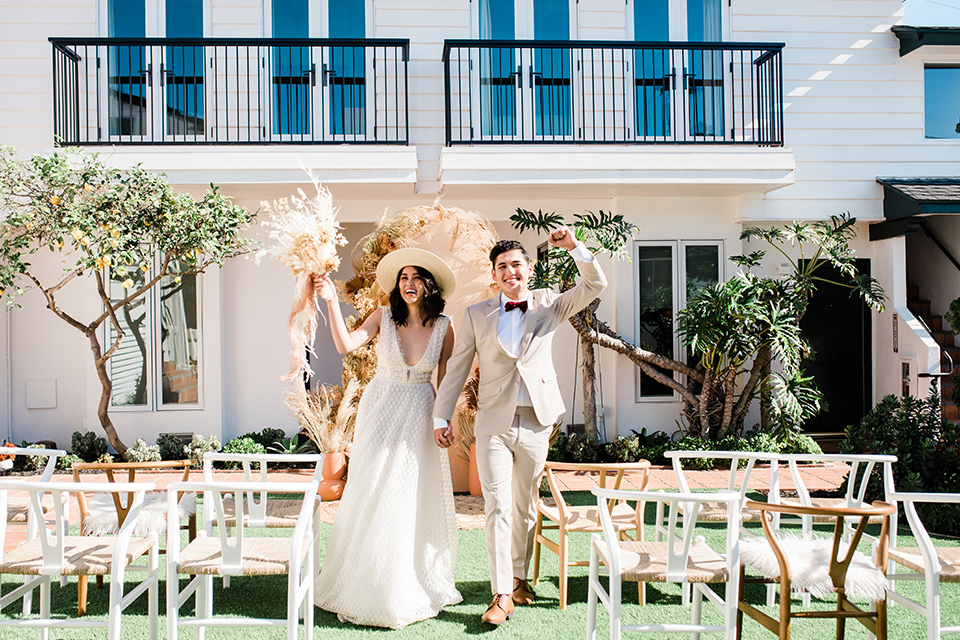 bride in a cream colored bohemian inspired gown with a gold crown, groom in a tan suit with a burgundy velvet bow tie