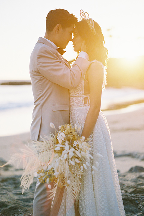 bride in a cream colored bohemian inspired gown with a gold crown, groom in a tan suit with a burgundy velvet bow tie, at the beach