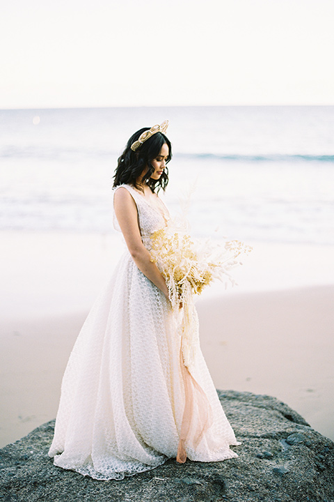 bride in a cream colored bohemian inspired gown with a gold crown