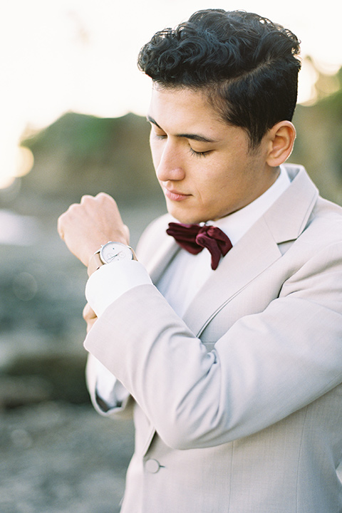 groom in a tan suit with a burgundy velvet bow tie