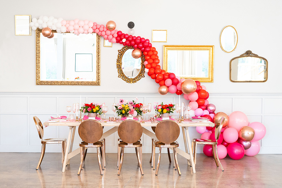 I-love-lucy-shoot-balloons-with-table-set-up-gold-chairs-and-table-with-cascading-pink-balloons-across-the-wall-and-pink-table-decor