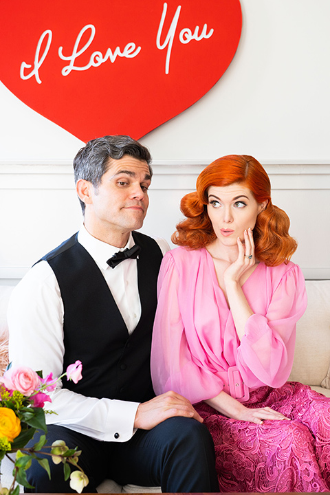 I-love-lucy-shoot-bride-and-groom-by-by-i-love-you-sign-bride-in-a-pink-wide-legged-pant-and-top-with-red-hair-and-red-lipstick-groom-in-a-white-and-black-tuxedo