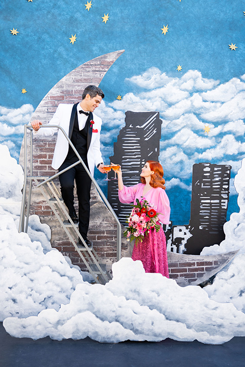 I-love-lucy-shoot-bride-and-groom-cheersing-by-moon-bride-in-a-pink-wide-legged-pant-and-top-with-red-hair-and-red-lipstick-groom-in-a-white-and-black-tuxedo