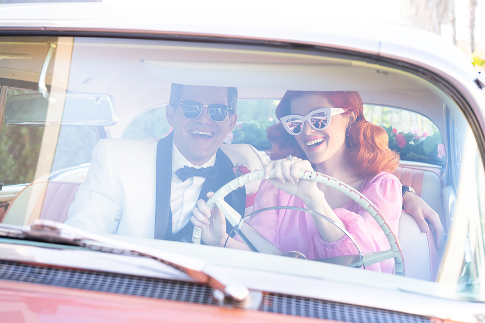 I-love-lucy-shoot-bride-and-groom-in-car-bride-in-a-pink-wide-legged-pant-and-top-with-red-hair-and-red-lipstick-groom-in-a-white-and-black-tuxedo