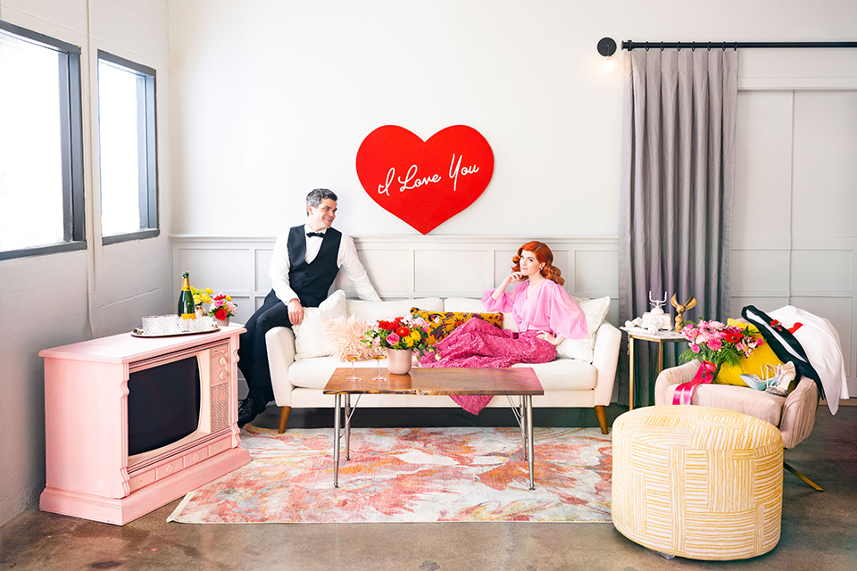 I-love-lucy-shoot-bride-and-groom-on-the-couch-bride-in-a-pink-wide-legged-pant-and-top-with-red-hair-and-red-lipstick-groom-in-a-white-and-black-tuxedo