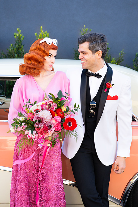 I-love-lucy-shoot-bride-and-groom-standing-by-car-bride-in-a-pink-wide-legged-pant-and-top-with-red-hair-and-red-lipstick-groom-in-a-white-and-black-tuxedo