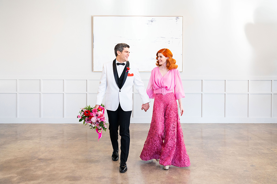 I-love-lucy-shoot-bride-and-groom-walking-towards-camera-bride-in-a-pink-wide-legged-pant-and-top-with-red-hair-and-red-lipstick-groom-in-a-white-and-black-tuxedo