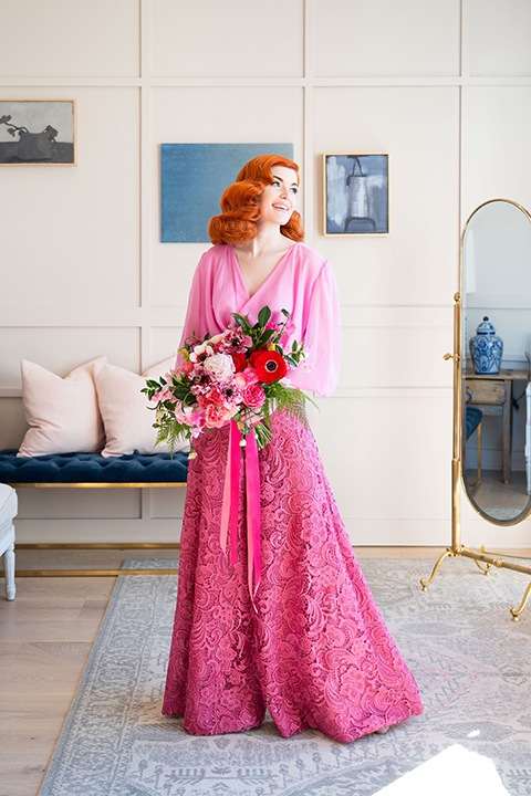 I-love-lucy-shoot-bride-standing-with-flowers-bride-in-a-pink-wide-legged-pant-and-top-with-red-hair-and-red-lipstick-groom-in-a-white-and-black-tuxedo