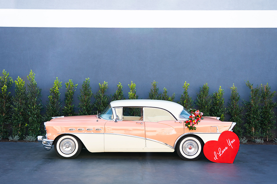 I-love-lucy-shoot-car-bride-in-a-pink-wide-legged-pant-and-top-with-red-hair-and-red-lipstick-groom-in-a-white-and-black-tuxedo
