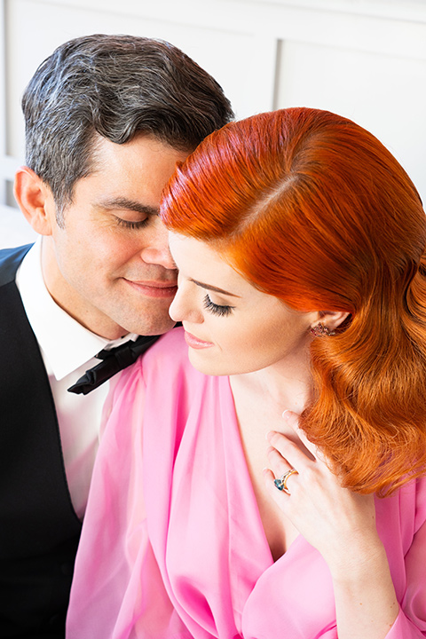 I-love-lucy-shoot-close-up-on-bride-and-groom-bride-in-a-pink-wide-legged-pant-and-top-with-red-hair-and-red-lipstick-groom-in-a-white-and-black-tuxedo