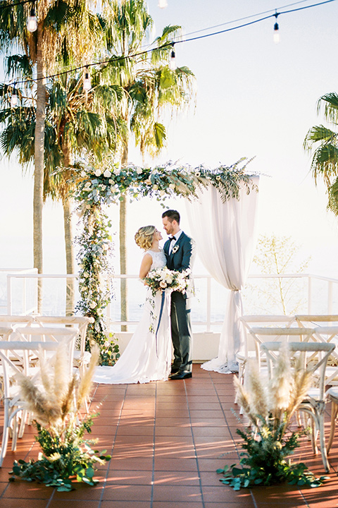The-Inn-at-Laguna-Beach-bride-and-groom-at-ceremony-bride-in-a-silk-dress-with-a-boat-neckline-and-hair-up-in-a-bun-and-groom-in-a-slate-blue-suit-with-a-matching-bow-tie