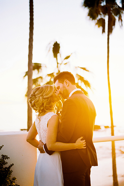 The-Inn-at-Laguna-Beach-bride-and-groom-at-sunset-bride-in-a-form-fitting-gown-with-a-high-slit-and-high-neckline-groom-in-a-grey-blue-suit-with-a-matching-bow-tie